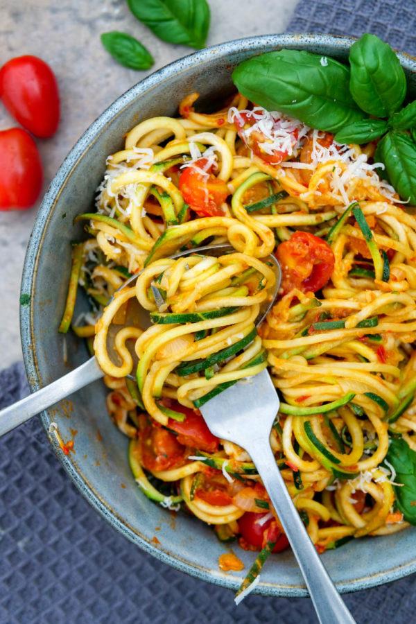Zucchini-Spaghetti mit Tomaten, Basilikum und Parmesan in der Schüssel