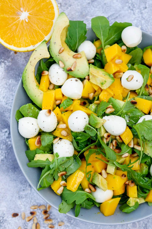 Schneller Rucola-Mango-Salat mit Avocado, Mozzarella und Pinienkernen. Perfekt für den Frühling