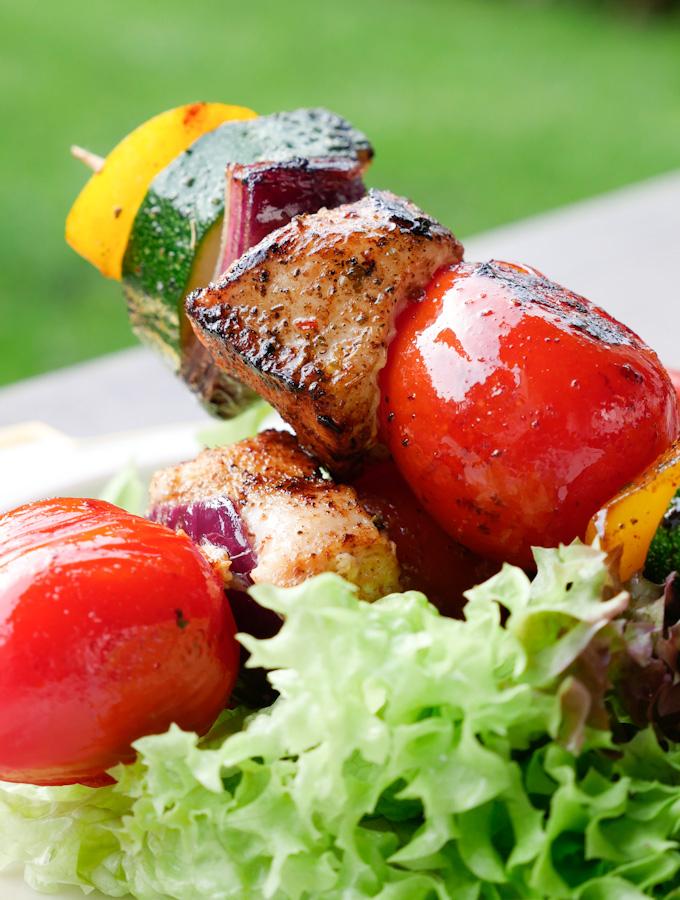 Grillspieß mit Hähnchen und Tomaten auf grünem Salat