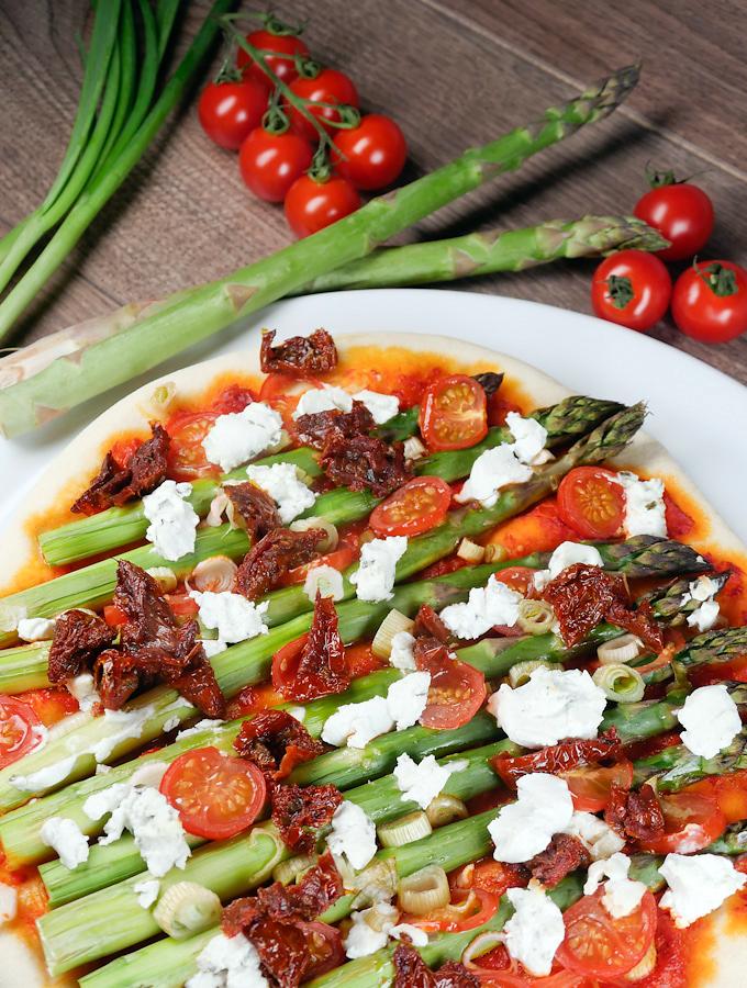 Selbstgemachte Pizza mit grünem Spargel, getrockneten Tomaten und Ziegenkäse