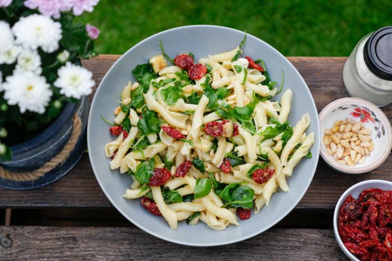 Italienischer Nudelsalat mit getrockneten Tomaten, Zucchini, Parmesan und Rucola