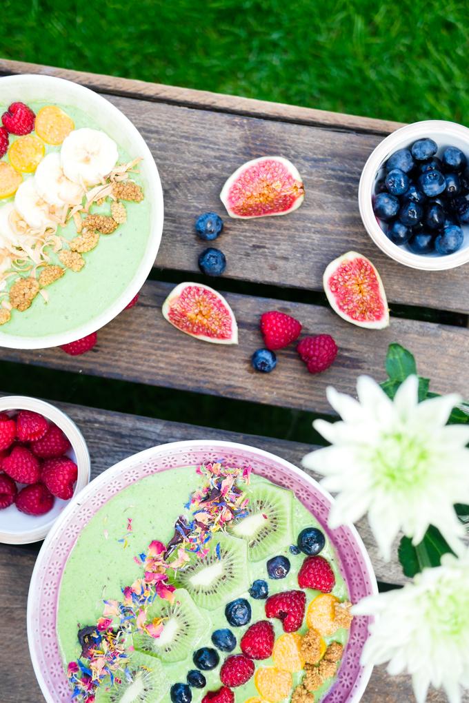 Grüne Smoothie Bowl mit Spinat und Mandelmilch - garniert mit essbaren Blüten und Maulbeeren