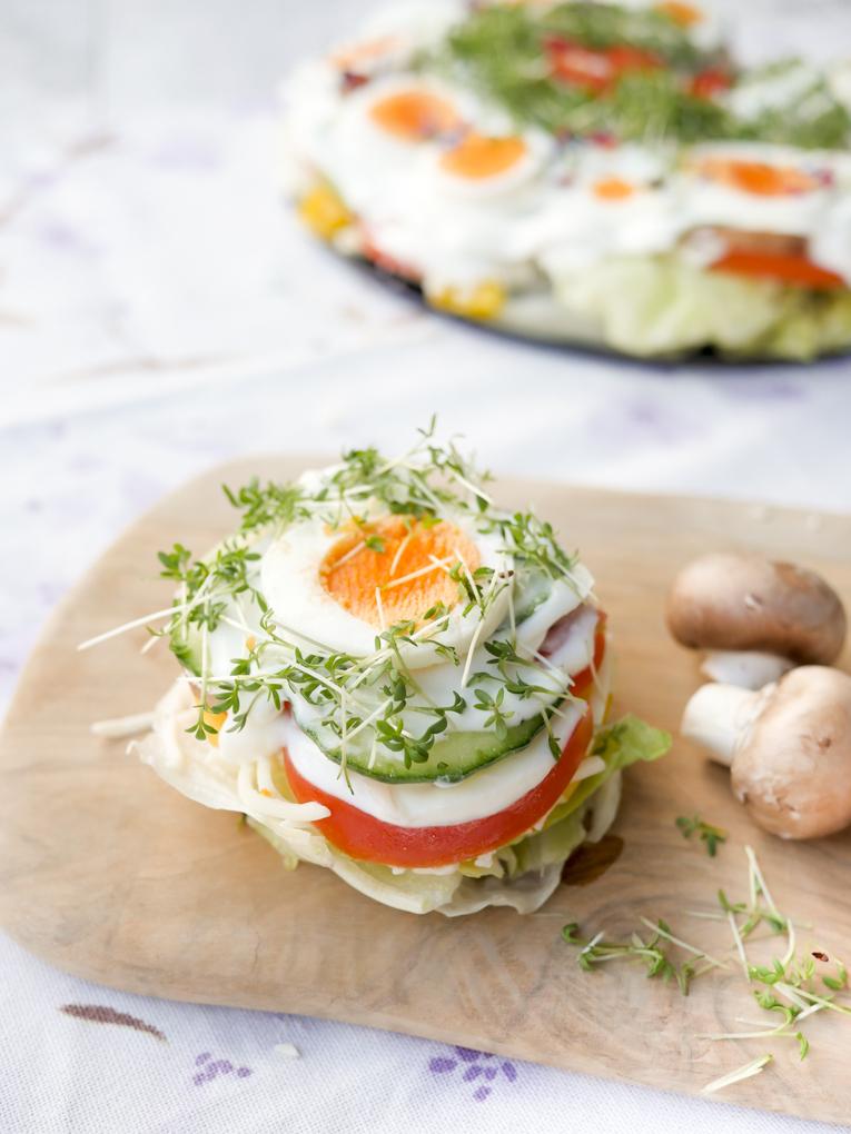 Gesunde Salattorte mit Eiern, Tomaten, Gurken und Champignons für Kinder