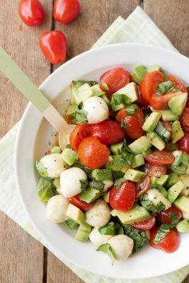 Salat mit Avocado, Tomaten und Mozzarella garniert mit Basilikum im tiefen Teller