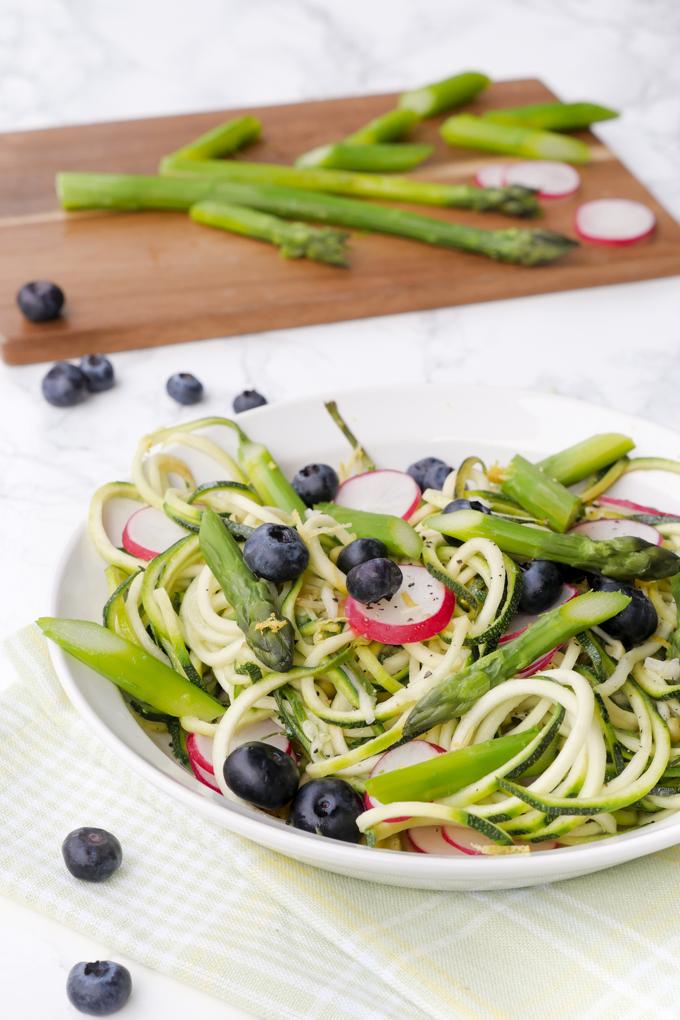 Farbenfrohe Zucchininudeln mit grünem Spargel, Erbsen, Radieschen und Blaubeeren