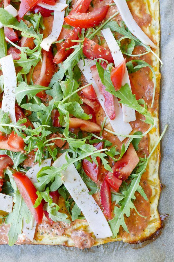 Low Carb Pizza mit Rucola, Tomaten, Pute und Sauce auf dem Backpapier