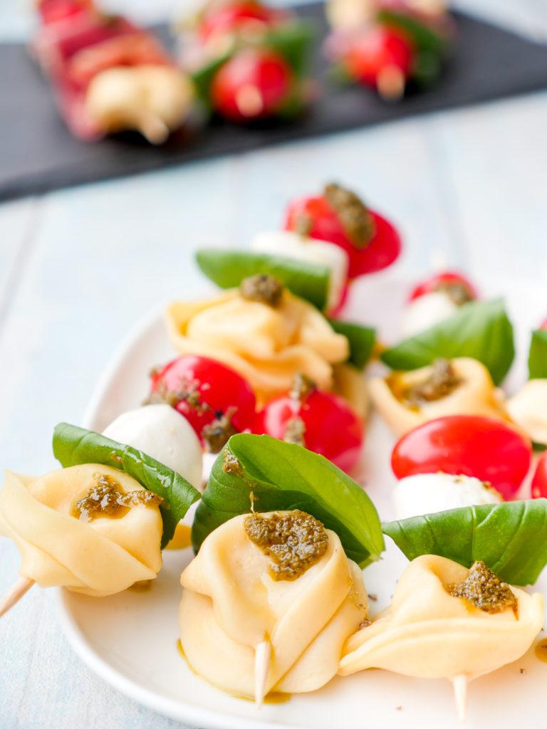 Tortellini-Salat am Spieß für das Silvesterbuffet - die bunten Spieße mit Tomaten, Mozzarella und Pesto sind ruckzuck zubereitet und ein Highlight auf dem Buffet GAUMENFREUNDIN FOODBLOG #tortellinisalat #tortellini #salat #rezept #schnell #einfach #6zutaten #partyrezept