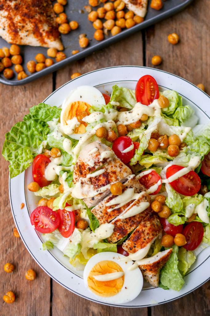 Gesunder Caesar Salad mit Hähnchen, Eiern, Tomaten und gerösteten Kichererbsen