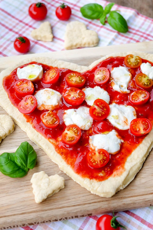 Einfaches Rezept für eine Pizza in Herzform - belegt mit Tomaten, Büffelmozzarella und Basilikum