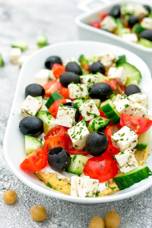 Gesunder Schicht-Dip zum Grillfest - Griechischer Hummus-Dip mit Oliven, Tomaten und Gurke