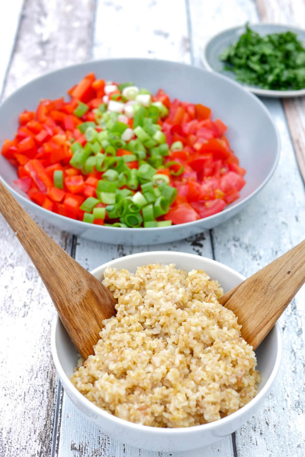 Bulgursalat Zubereitung mit Bulgur, Paprika, Tomaten und Frühlingszwiebeln in Schüsseln