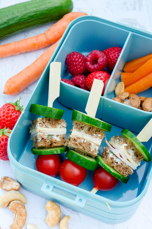 Gesunde Kinder-Lunchbox mit Brotspießen, Himbeeren, Erdbeeren, Möhren und Cashewnüssen