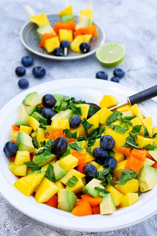 Farbenfroher Sommersalat mit Heidelbeeren, Mango, Avocado, Paprika und Minze