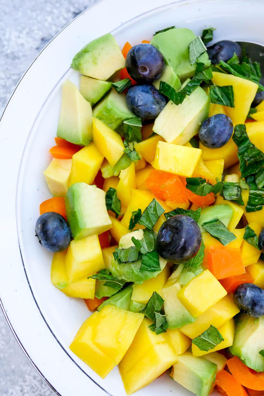 Sommersalat mit Mango, Avocado, Heidelbeeren, Paprika, Minze und einem frischen Limettendressing