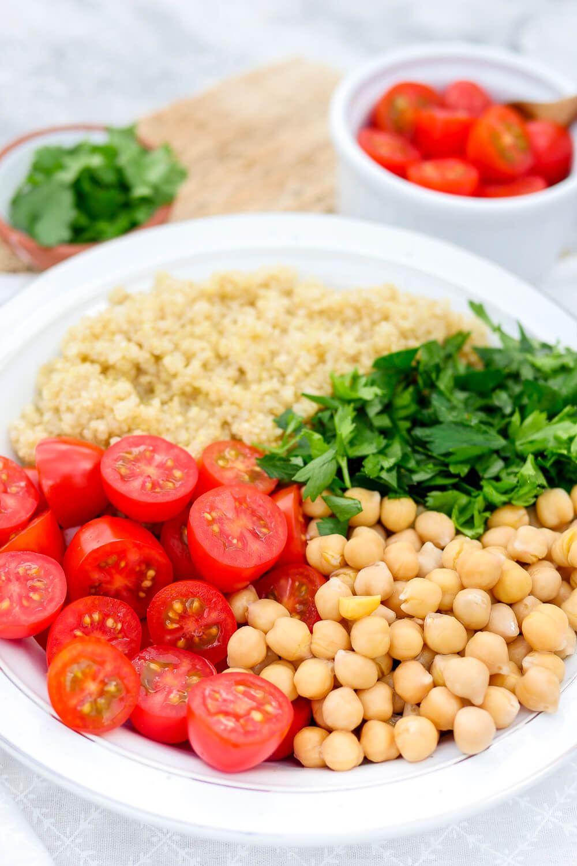 Gesunder Sommersalat mit Tomaten, Quinoa, Kichererbsen und Petersilie.