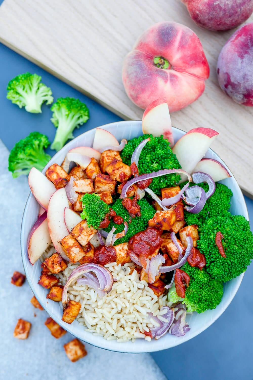 Ganz schnelles Rezept für eine BBQ Tofu-Bowl mit Brokkoli, Pfirsich, Reis, Zwiebeln und in BBQ Sauce mariniertem Tofu