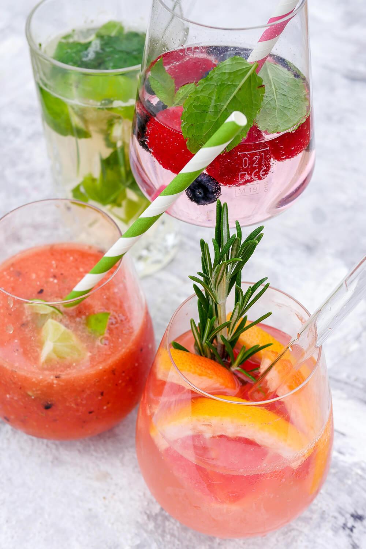 Vier alkoholfreie Cocktails im Glas mit Melone, Grapefruit, Minze und Beeren