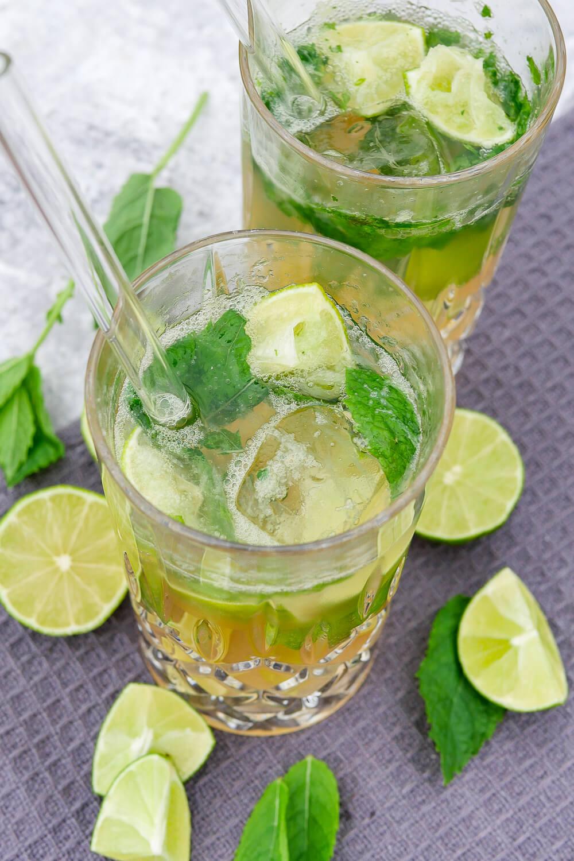Alkoholfreier Caipirinha mit Ginger Ale und Maracujasaft, dekoriert mit Limette und Minze im Glas