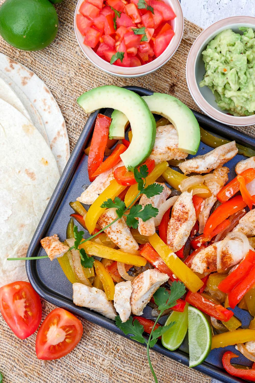 Ein-Blech Fajitas mit Hähnchen, Paprika, Zwiebeln, Tortillas und Koriander - ein schnelles 10-Minuten-Rezept für die ganze Familie