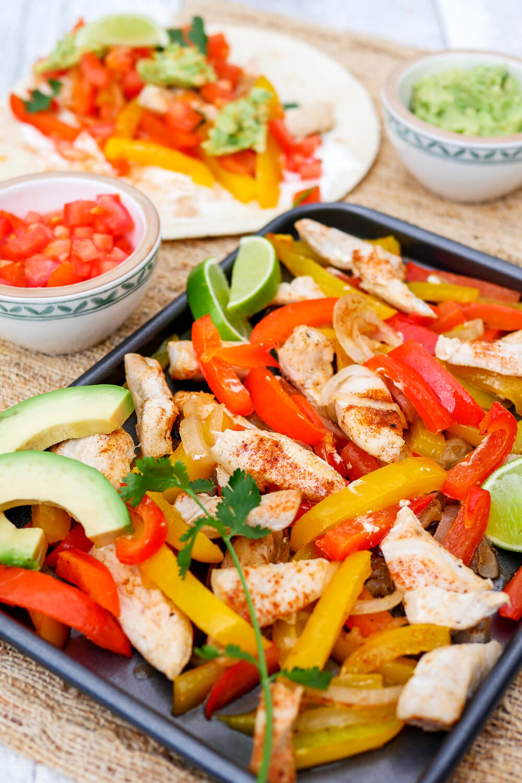 Ein-Blech Hähnchen-Fajitas mit Paprika, Zwiebeln, Koriander und Tortillas zum Selberbelegen