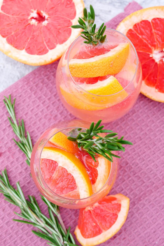 Pink Tonic Cocktail mit Grapefruit, Rosmarin und Tonic dekoriert mit Rosmarinzweigen im Glas