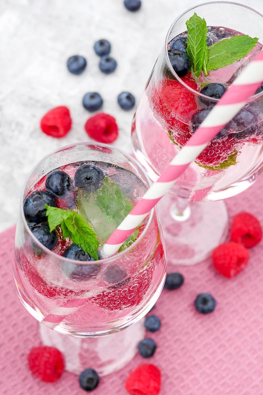 Alkoholfreier Cocktail mit Wild Berry, Heidelbeeren, Himbeeren und Minze mit Strohhalm im Glas