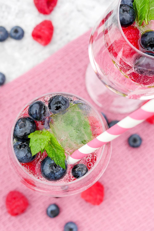 Cocktail mit Heidelbeeren, Minze und Wild Berry mit Strohhalm im Glas