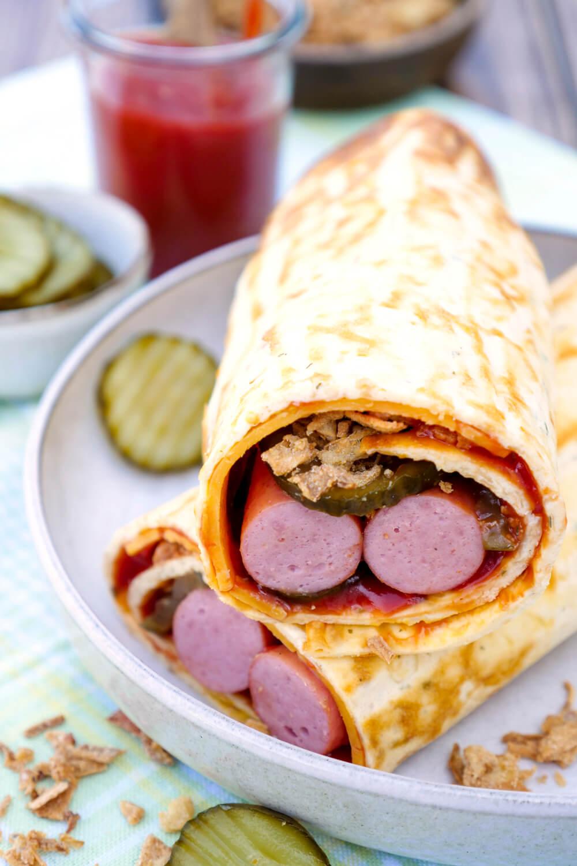 Rezept für meine beliebte Low Carb Hotdog Rolle mit Würstchen, Cheddar, Ketchup, Röstzwiebeln und Gurken