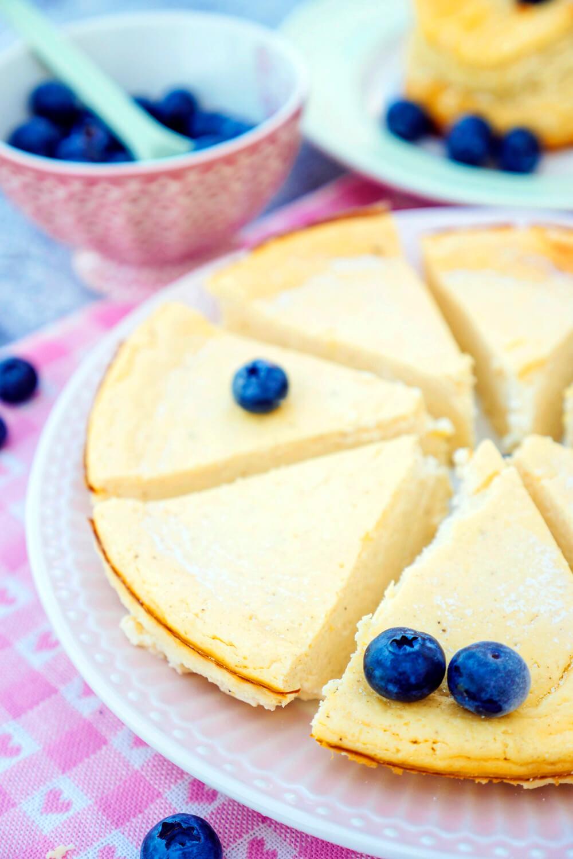 Low Carb Käsekuchen mit Heidelbeeren in Stücken geschnitten auf dem rosa Teller