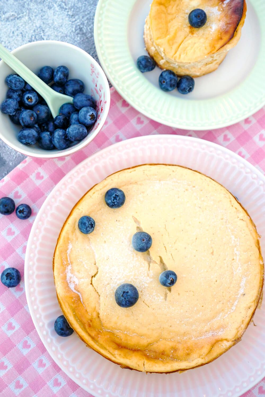 Kleiner Low Carb Cheesecake mit Heidelbeeren und Puderzucker auf dem rosa Teller