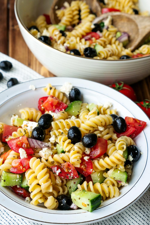 Sommerlicher Nudelsalat griechischer Art mit Tomaten, Gurken, Oliven, Feta und super würzigem Knoblauch Dressing