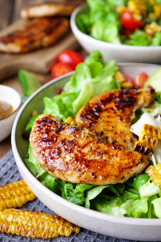 Mariniertes Hähnchen mit Honig-Senf-Dressing auf gemischtem Salat mit Avocado und Mais