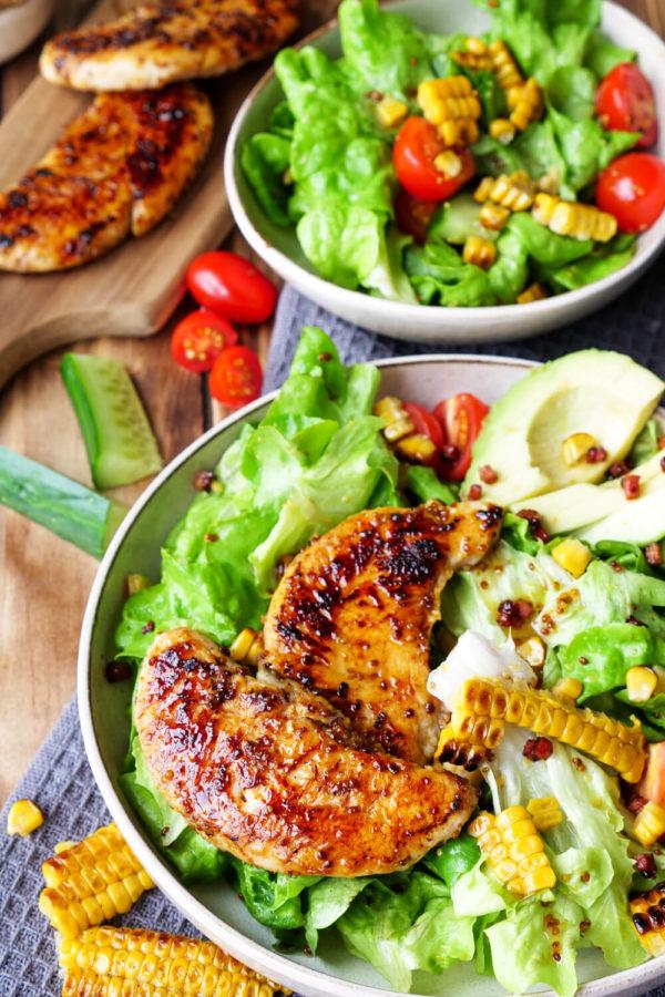 Salat mit Hähnchen, Maiskolben, Gurke, Avocado und Speck
