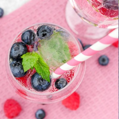 Wild Berry Dreams Cocktail mit Beeren, Minze und Himbeeren mit Strohhalm im Glas