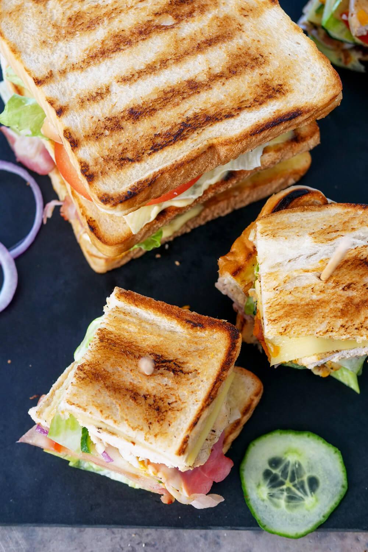 Einfaches Club Sandwich Rezept mit Putenbrustfilet, Speckstreifen, Tomaten, Gurken, Eiern, Salat, Käse, Mayonnaise und Senf