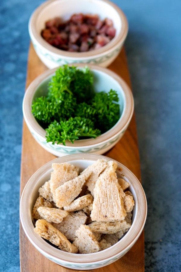 Toppings für eine Kartoffelsuppe - Speckwürfel, Croûtons und Petersilie)