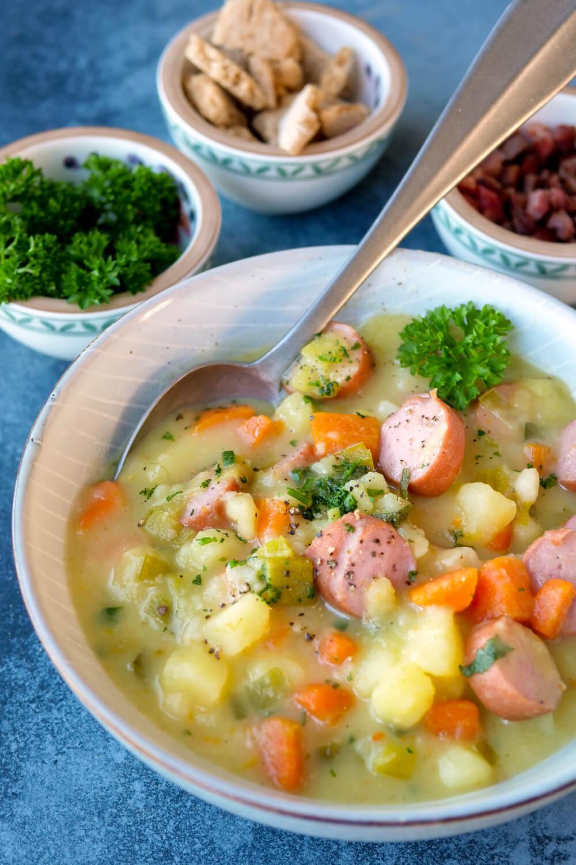 Kartoffelsuppe mit Würstchen, Gemüse und Petersilie in der tiefen Schüssel