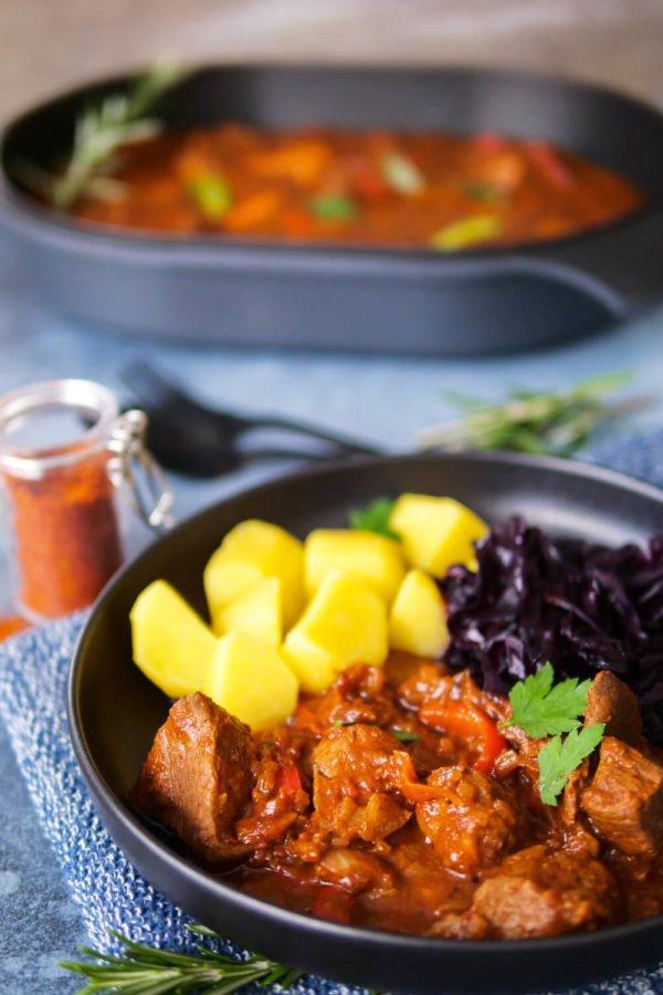 Gulasch mit Kartoffeln und Rotkohl auf dem tiefen Teller