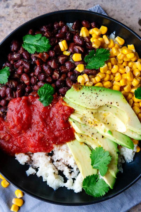 Farbenfrohe Bowl mit Blumenkohlreis, Mais, Bohnen, Avocado und Salsa