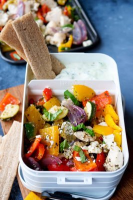 Lunchbox mit Paprika, Hähnchen, Zwiebeln, Zucchini und Tzatziki