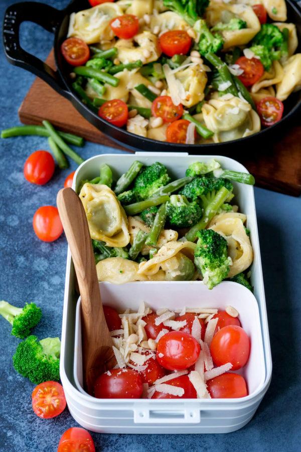 Lunchbox mit Tortellini und Gemüse aus Brokkoli, Bohnen und Tomaten mit Pfanne im Hintergrund