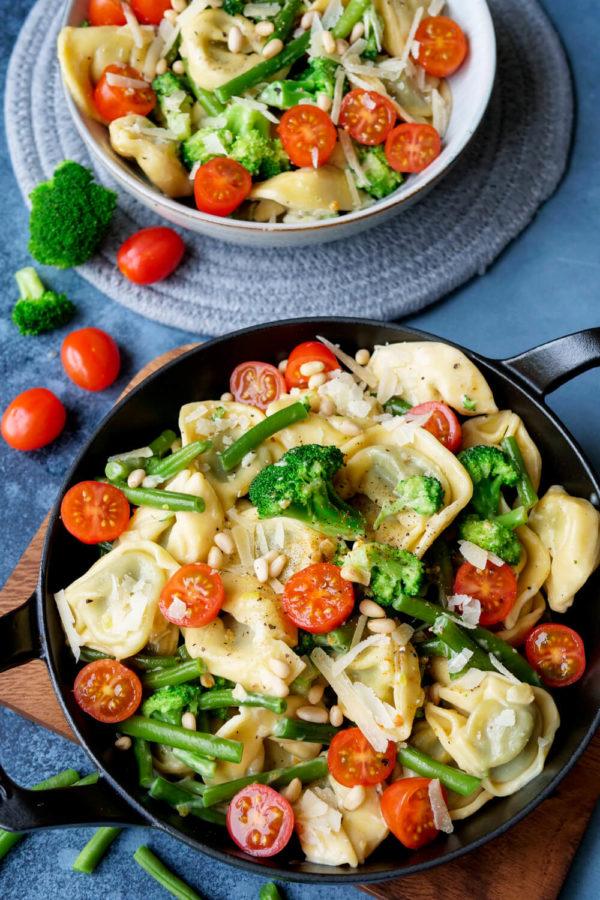 Tortellini-Pfanne mit grünen Bohnen, Tomaten, Brokkoli und Pinienkernen auf dem Holzbrett