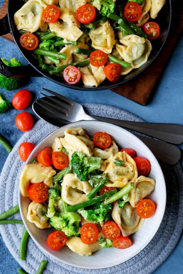Tortellini mit Brokkoli, Bohnen und Tomaten auf dem tiefen Teller