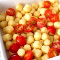 Gnocchi mit halbierten Tomaten in der weißen Auflaufform