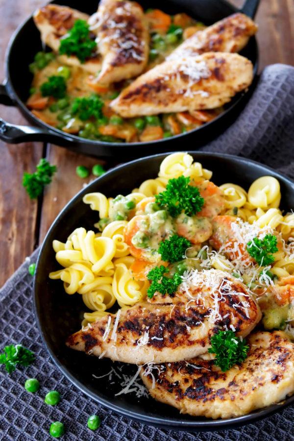 Hähnchen mit Gemüse und Nudeln auf dem Teller, dekoriert mit Petersilie