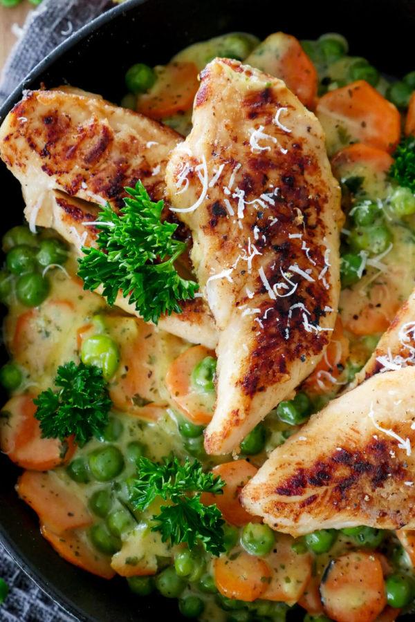 Cremiges Hähnchen mit Erbsen und Möhren Gemüse in der Pfanne