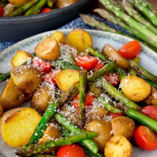Kartoffeln mit grünem Spargel, Tomaten und Parmesan auf dem Teller und in der Pfanne