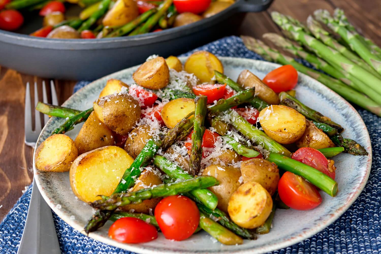 Grüner Spargel mit Kartoffeln, Tomaten und Parmesan auf dem Teller
