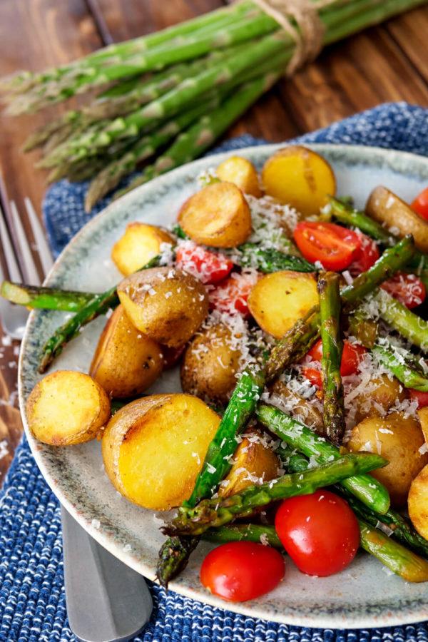 Kartoffeln mit grünem Spargel, Tomaten und Parmesan auf dem Teller