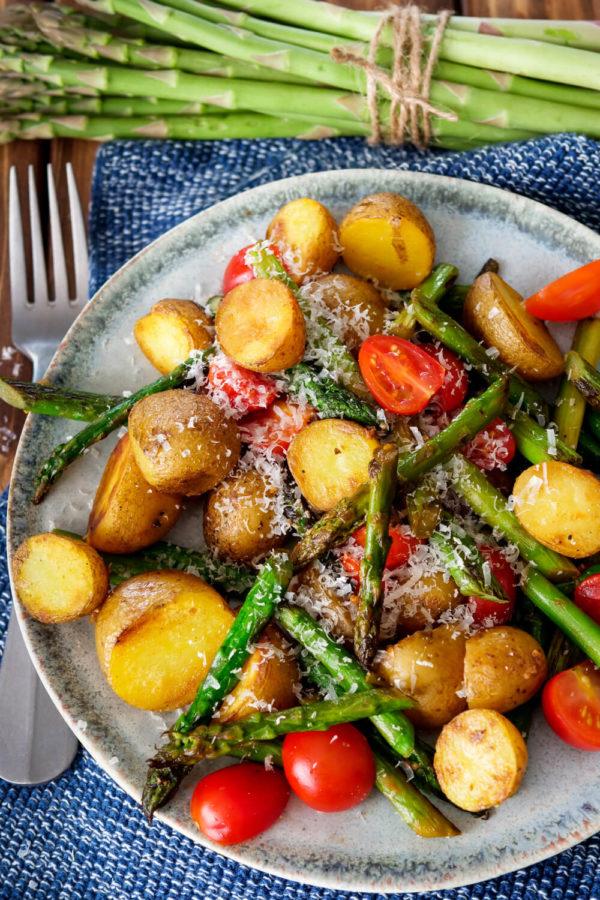 Kartoffeln mit grünem Spargel, Tomaten und Parmesan auf dem Teller, dazu grüne Spargelstangen